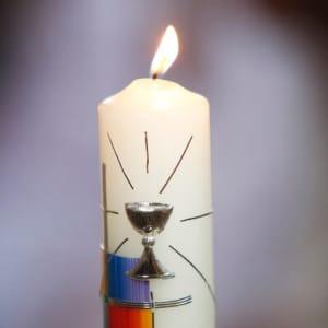 Brennende Kommunionkerze mit Kreuz und Kelch Motiv