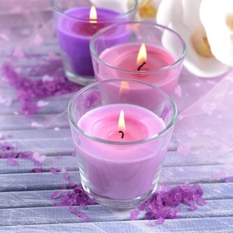 Schöne bunte Kerzen im Glas - orchideefarbend