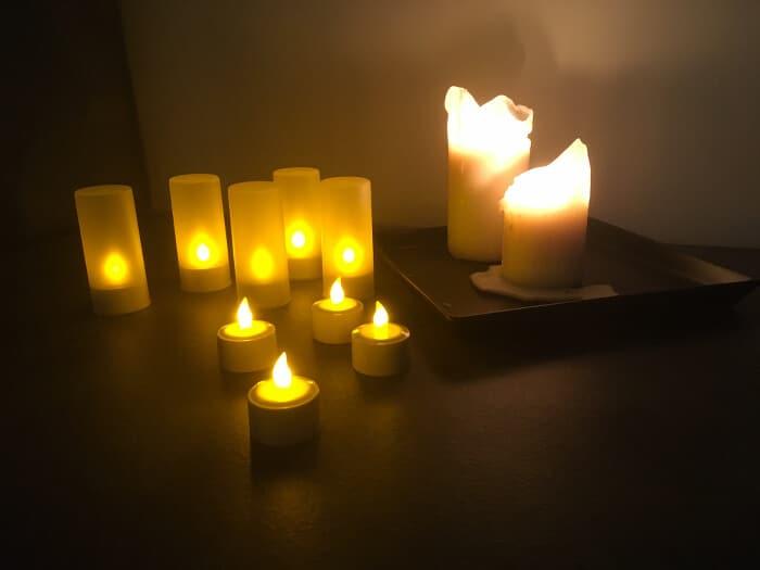 Teelichter mit Batterie zum aufladen neben echten Kerzen zur Deko
