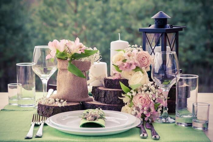 Selbstgestaltete Hochzeits-deko mit Blumen, Kerzen, Laternen und Baumscheiben