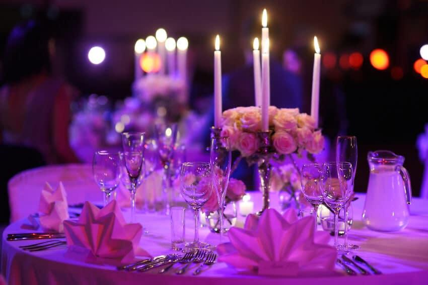 Elegant gedeckter Tisch für die Hochzeitsfeier mit silbernen 5-armigen Spitzkerzenständern