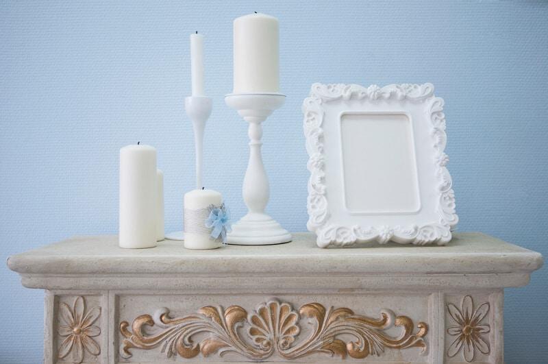 Kerzenhalter mit weißen Kerzen und Bilderrahmen als Deko auf einer Kommode