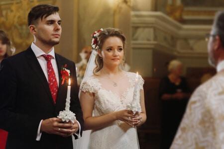 Braut und Bräutigam halten beide die symbolische Kerze in der Hand
