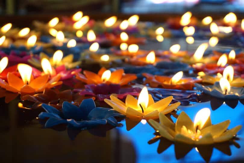 Bunte Kerzen in Blütenform auf dem Wasser