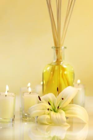 Duftsticks in Flasche mit Kerzen und Lilien