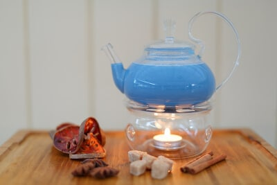 Durchsichtige Teekanne auf einer Kerze mit leckerem Punch - Zimt, Anis, Kandizucker und Onrangen