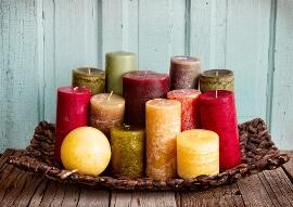 Ein Bastkorb voller bunter Kerzen in allen Farben und Formen