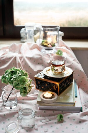 Gedeckter Tisch zu Teezeit mit Deko und kleinen Teelichthaltern