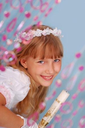Kleines Mädchen bei ihrer Konfirmation mit Kerze in den Händen