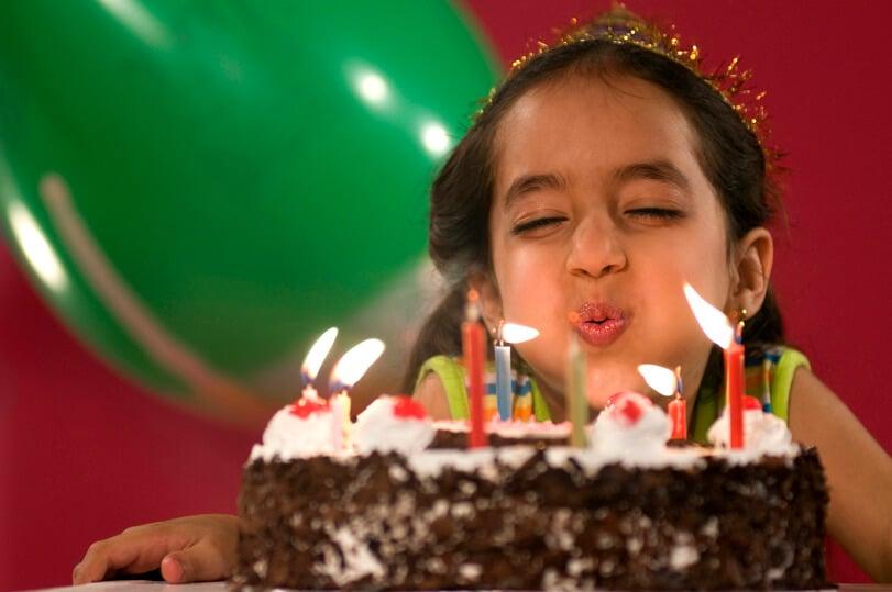 Kleines Mädchen pustet gerade die langen, dünnen Kerze auf ihrem Kuchen aus
