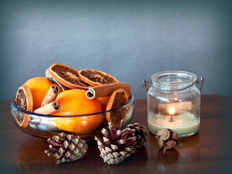 Perfekt angerichtetes Windlichtglas mit Sand, Deko und Kerze