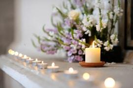 Reihe von vielen kleinen Kerzen und Teelichtern auf dem Kaminsims