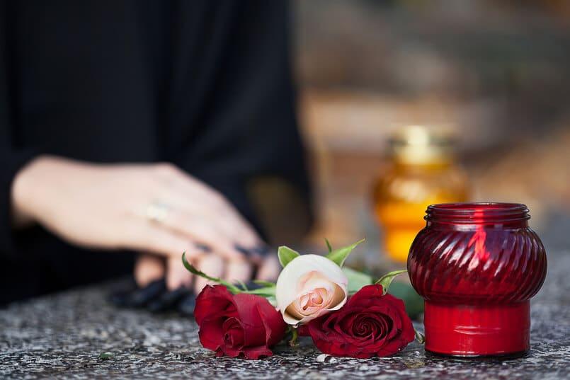 Rote Kerze im Glas mit Rosen zur Trauer um den verstorbenen