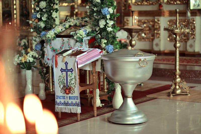 Taufaltar und Becken mit Blumen geschmückt und Kreuz-Symbol
