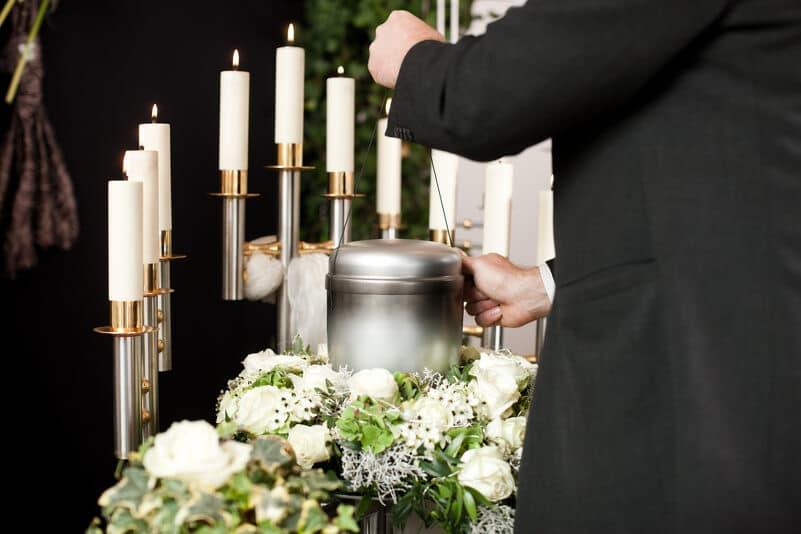 Urnenbestattung und viele brennende Kerze um der verstorbenen Seele den Weg zu weisen