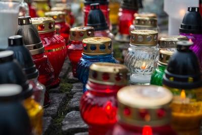 Viele verschiedenfarbige Grableuchten in Gläsern mit Deckeln