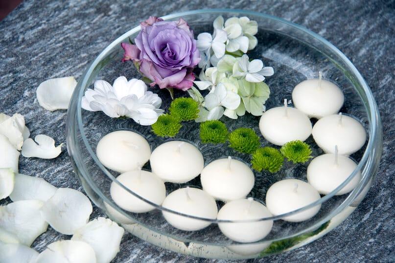 Weiße Schwimmkerzen mit Blumen in Dekoschale